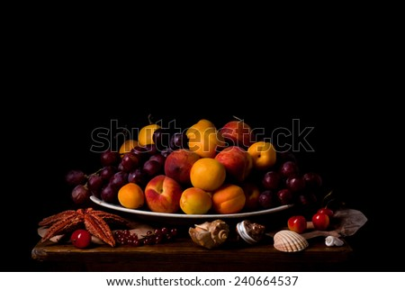 Fruit dish surrounded by sea shells, starfish and berries on dark background. Still life in vintage style - stock photo