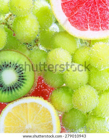 Fruit floating in the water with bubbles: green grapes, kiwi, lemon and grapefruit  - stock photo