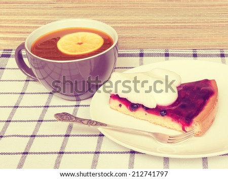 Fruit jelly cake and cup of tea with lemon. Toned image.  - stock photo