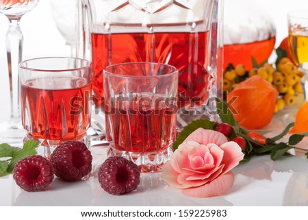 Fruit liqueurs from raspberries and cherries - stock photo