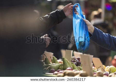 Fruit market trader handing a bag of goods over to a paying customer - stock photo
