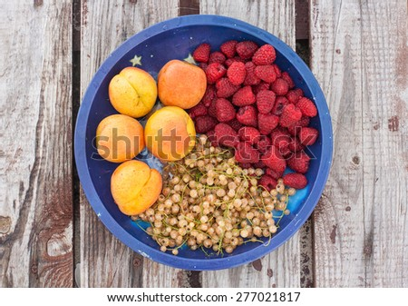 Fruit mix with fresh apricots, raspberries and white currants on the plate and wooden surface, top view - stock photo