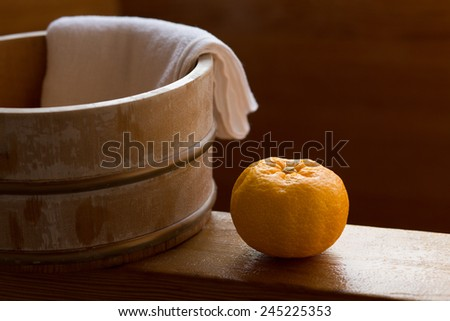 Fruit of yuzu on the edge of a wooden bath at Japanese onsen. Bath with yuzu, also known as yuzuyu and yuzuburo, traditionally taken during winter solstice, a custom that dates to early 18th century. - stock photo