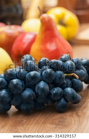 Fruit on old plank, grape in foreground, pears and apples in background - stock photo