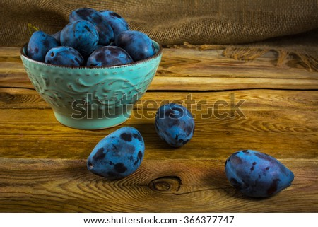 Fruit plums prunes in turquoise cup on old dark wooden background. Selective focus. Fruit. Fruits. Plum - stock photo