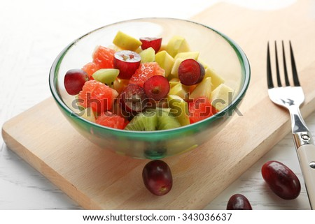 Fruit salad in glass bowl, on light wooden background - stock photo