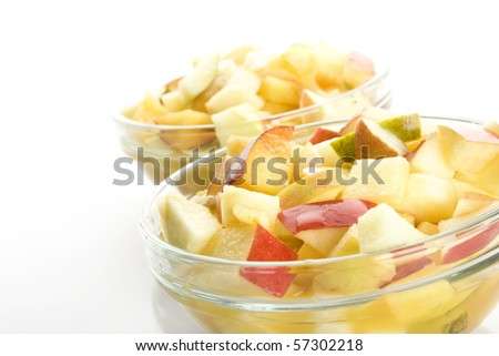 Fruit salad with apples, oranges, peaches, pears and orange juice. Decomposed in two glass plates. Isolated on white background - stock photo