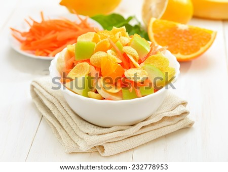 Fruit salad with cornflakes in bowl on white wooden table, closeup view - stock photo