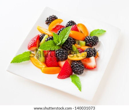 Fruit salad with fresh strawberries, blackberries,  kiwis and  kumquats on a plate on light background. Healthy eating, berry dessert. selective focus. - stock photo