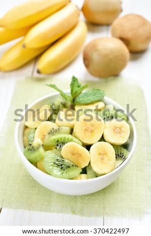 Fruit salad with kiwi and banana in white bowl - stock photo