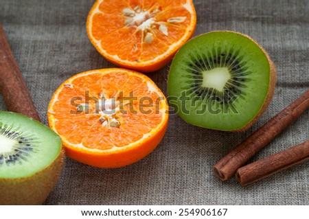 Fruit set - orange tangerine half,  kiwi and cinnamon sticks on hessian linen fabric cloth - stock photo