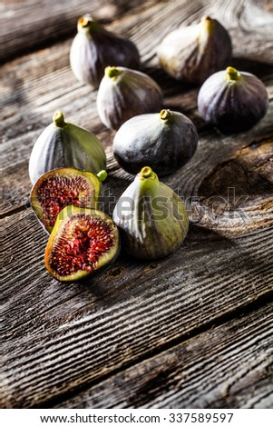fruit still-life - top view of several organic figs,whole and cut,on wood background for genuine texture effect and food freshness - stock photo