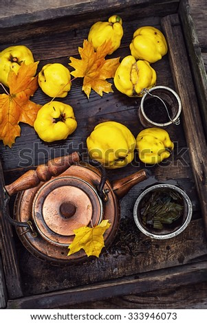 Fruit tea with quince.Fashion copper kettle with tea and quince in wooden box - stock photo