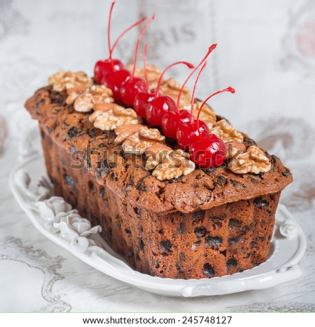 Fruitcake decorated walnuts, almond and cocktail cherries on the white plate  - stock photo