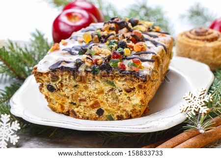 Fruitcake with dried fruits and nuts in christmas setting - stock photo