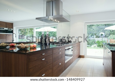 Fruits and bottles on countertop with wooden drawers in modern kitchen - stock photo