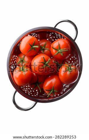 Fruits and vegetables: fresh red tomatoes in a steel colander, overhead view, isolated on white background - stock photo