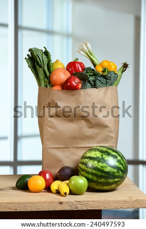 Fruits and vegetables in grocery bag and on wooden table - stock photo