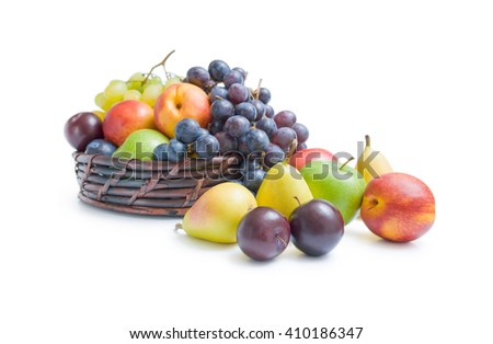 Fruits arrangement. Mix of various fresh ripe fruits plums apples pears peaches and grapes placed in a wicker basket and around isolated on a white background. - stock photo