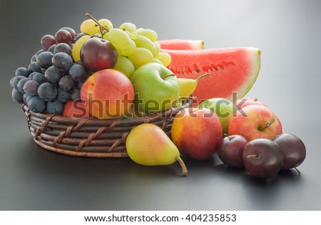 Fruits arrangement. Various fresh ripe fruits arranged in a wicker basket and around on neutral gray gradient background - stock photo
