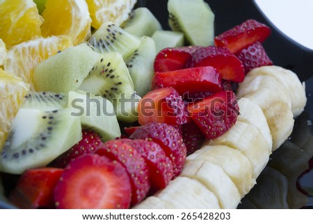 Fruits in black ceramic plate - stock photo