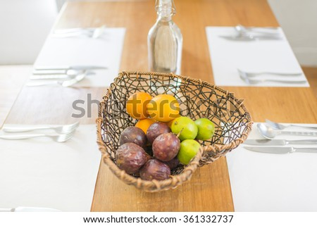 Fruits in heart shape basket on dining table with dishware on white napkin - stock photo