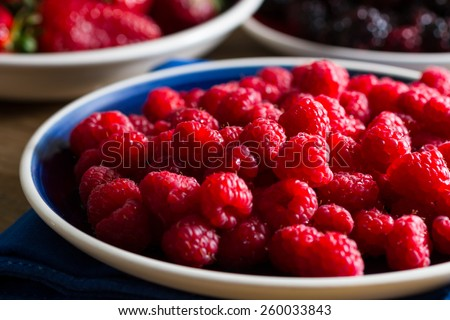 Fruits of the forest:  raspberries. Shallow depth of field. Strawberries and blackberries in the background. - stock photo