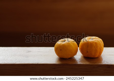 Fruits of yuzu on the edge of a wooden bath at Japanese onsen. Bath with yuzu, also known as yuzuyu and yuzuburo, traditionally taken during winter solstice, a custom that dates to early 18th century. - stock photo