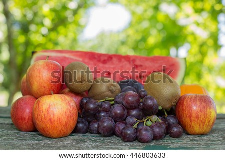 fruits on wooden table, outdoor, in the garden - stock photo