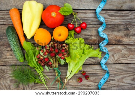 Fruits, vegetables and in measure tape in diet on wooden background - stock photo
