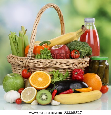 Fruits, vegetables, vegetarian groceries and healthy beverages in a shopping basket - stock photo