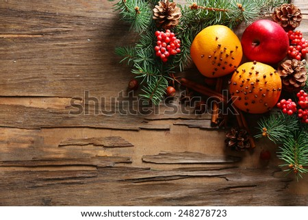 Fruits with nuts, spices and sprigs of Christmas tree on rustic wooden background - stock photo
