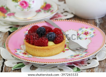 Fruity tartelette with custard, fresh raspberries and blueberries on pink plate  - stock photo