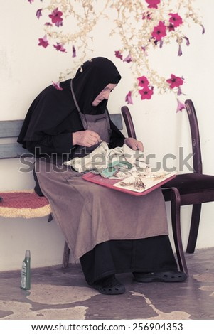 FRUSKA GORA, SERBIA - AUGUST 04 2014: an elder nun is polishing the brass. in the courtyard of Grgeteg Monastery on Fruska Gora mountain in the northern Serbia. - stock photo