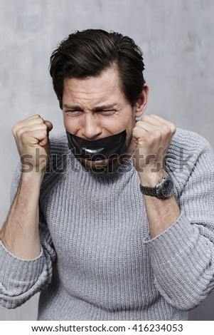 Frustrated and censored guy with duct tape - stock photo