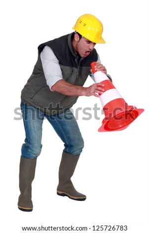 Frustrated builder shouting into traffic cone - stock photo
