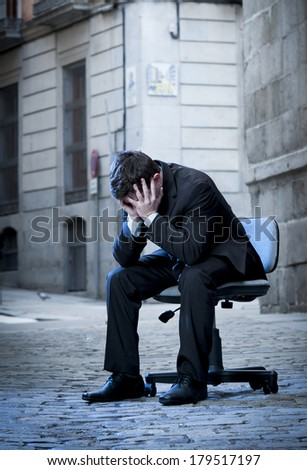 frustrated Business Man sitting on Office Chair on Street in stress and crying - stock photo