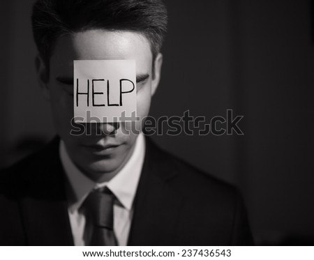 Frustrated business man with adhesive note on his forehead - stock photo