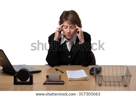 Frustrated business woman sitting at desk with hands on temples with computer on white background - stock photo