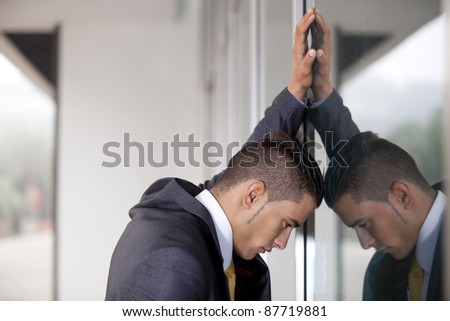 frustrated businessman banging his head at the office window - stock photo
