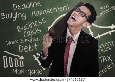 Frustrated businessman cutting his neck with a saw in front of blackboard - stock photo