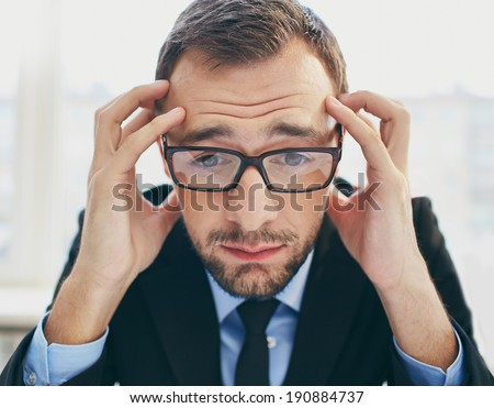 Frustrated businessman in eyeglasses touching his head - stock photo
