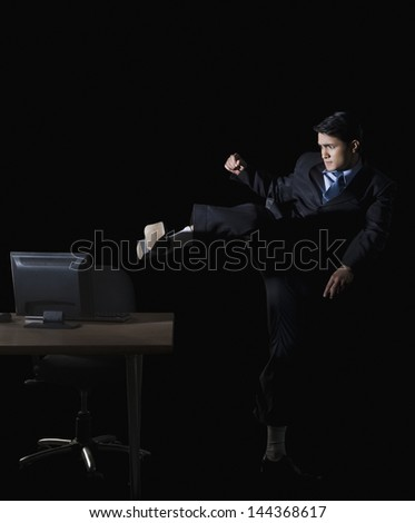 Frustrated businessman kicking a desktop pc - stock photo