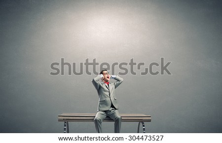 Frustrated businessman on bench closing ears with hands - stock photo