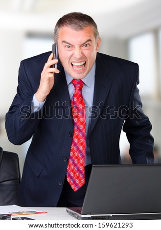 Frustrated businessman screaming into the mobile phone while in the office. - stock photo