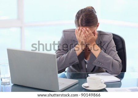 Frustrated businesswoman crying in her office - stock photo