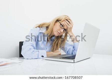 Frustrated businesswoman looking at laptop in office - stock photo
