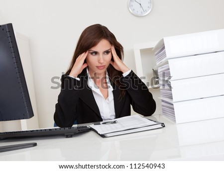Frustrated businesswoman with stack of folders on computer desk - stock photo