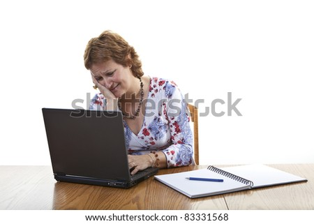 Frustrated businesswoman working on a laptop - stock photo