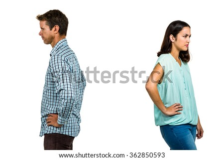 Frustrated couple ignoring each other while standing against white background - stock photo